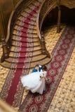 Brudgummen bär bruden längs den gamla barocka slotten Fotografering för Bildbyråer