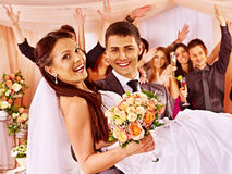 Brudgummen bär bruden på hans händer Royaltyfri Bild