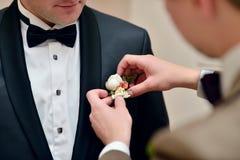 Brudgummen bär en dräkt inomhus Arkivfoto