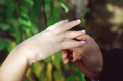 Brudgummen bär en vigselring på brudens finger royaltyfria foton