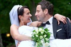 Brudgummen bär hans brud Arkivbild