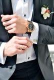 Brudgummen bär manschettknappar inomhus Arkivfoto