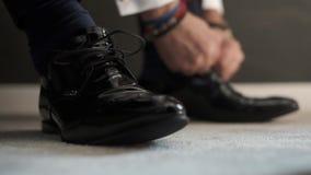 Brudgummen band snör åt på skorna Mannen bär skor arkivfilmer