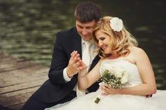 Brudgummen beundrar brudens arm med en vigselring, medan sitta på t royaltyfri foto