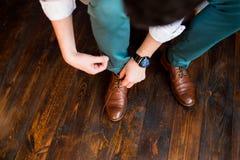 Brudgummen binder skosnören i hans bruna skor Royaltyfri Fotografi