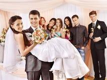 Brudgummen bär bruden på hans händer. Arkivbilder