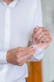 Brudgummen fäster en skjorta arkivfoto