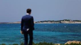 Brudgummen går kusten med en bukett stock video