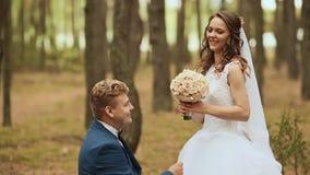 Brudgummen ger bruden en bukett av hennes anseende på ett knä på naturen Den lyckliga brudgummen lyfter bruden som cirklar henne arkivfilmer
