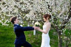Brudgummen ger bruden en härlig bröllopbukett av rosor arkivfoto