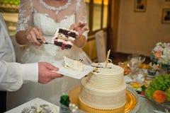 Brudgummen hjälper bruden att dela kakan in i stycken 520 Arkivbild