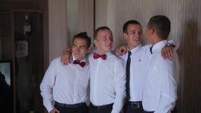 Brudgummen i den vita skjortan och bandet med hans vänner står i rad i omfamning och ordnar till för att fotograferas på kameran arkivfilmer