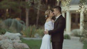 Brudgummen i en dräkt som kramar bruden i lager videofilmer