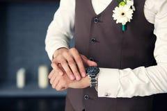 Brudgummen i en waistcoat som ser hans klocka Royaltyfri Bild