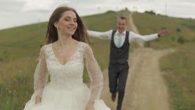 Brudgummen kör för bruden på kullar för ett berg binder crystal smycken f?r parcravaten br?llop lycklig familj stock video