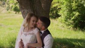 Brudgummen kommer till att charma den blonda bruden med buketten bak henne l?ngsam r?relse arkivfilmer