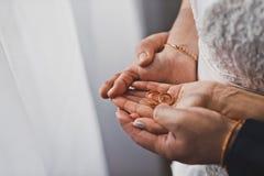 Brudgummen kramar brudhänderna med vigselringar 1253 Royaltyfri Bild