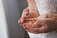 Brudgummen kramar brudhänderna med vigselringar 1254 Arkivbilder