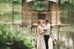 Brudgummen kysser bride& x27; s-panna, medan hon lutar till honom som ler Royaltyfria Foton