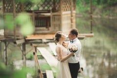 Brudgummen kysser bride& x27; s-panna, medan hon lutar till honom som ler Fotografering för Bildbyråer