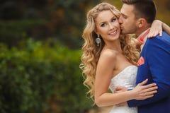 Brudgummen kysser bruden i en gräsplan parkerar i sommaren Royaltyfria Bilder