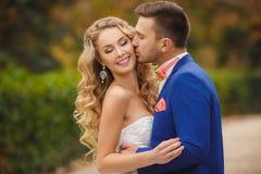 Brudgummen kysser bruden i en gräsplan parkerar i sommaren Arkivfoto