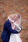 Brudgummen kysser bruden som bär en skyla Arkivbild