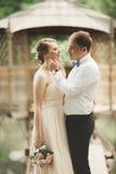 Brudgummen kysser brudens panna, medan hon lutar till honom som ler Royaltyfri Bild