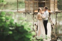 Brudgummen kysser brudens panna, medan hon lutar till honom som ler Arkivbilder