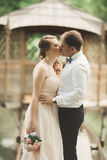 Brudgummen kysser brudens panna, medan hon lutar till honom som ler Royaltyfri Fotografi