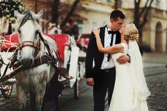 Brudgummen kysser en brud bak en vagn royaltyfri fotografi