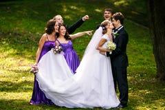 Brudgummen kysser en brud medan hans vängrimaser bak honom Arkivbild
