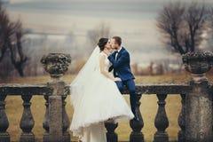 Brudgummen kysser ett brudsammanträde med henne på balkongen med en grea arkivbilder