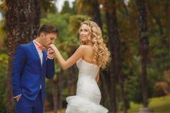 Brudgummen kysser handen av bruden i gräsplan parkerar Arkivbild
