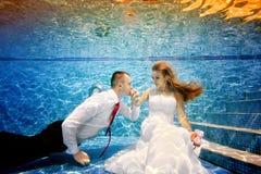 Brudgummen kysser handen av bruden som är undervattens- i pölen Stående Skjuta under vatten Royaltyfria Foton