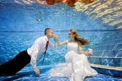 Brudgummen kysser handen för brud` s, som sitter undervattens- längst ner av pölen Stående Royaltyfria Bilder