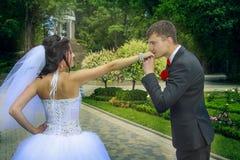 Brudgummen kysser hans hand för brud` s Fotografering för Bildbyråer