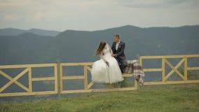Brudgummen med bruden sitter på staketet nära bergkullar binder crystal smycken f?r parcravaten br?llop familj lager videofilmer