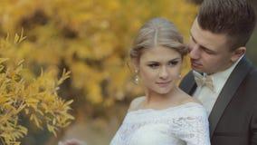 Brudgummen med flugan kysser försiktigt den unga bruden stock video