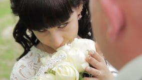 Brudgummen omfamnar bruden i en parkera i solskenet stock video