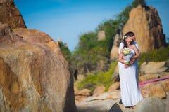 Brudgummen omfamnar bruden mot ett härligt landskap, berg och havet arkivfoto