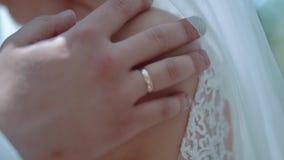 Brudgummen omfamnar bruden, passerar hennes hand över hennes skuldror, närbild lager videofilmer