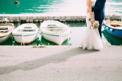 Brudgummen omfamnar brudfartygmooragen Gifta sig i Montenegro royaltyfri bild