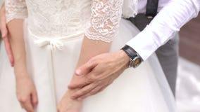 Brudgummen omfamnar försiktigt bruden, närbild av händer arkivfilmer
