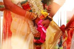 Brudgummen rymmer brudhanden i södra indisk traditionell bröllopceremoni arkivbilder