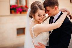 Brudgummen rymmer den härliga bruden i hans armar royaltyfria bilder
