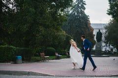 Brudgummen rymmer den vridna bruden i hans armar och Royaltyfri Foto