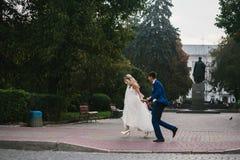 Brudgummen rymmer den vridna bruden i hans armar och Arkivbild