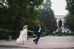 Brudgummen rymmer den vridna bruden i hans armar och Royaltyfria Bilder