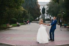 Brudgummen rymmer den vridna bruden i hans armar och Royaltyfri Bild